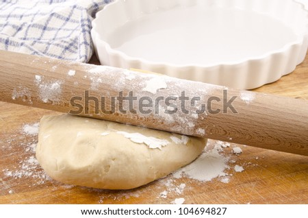 dough to make a quiche and a kitchen roll on a wooden board - stock photo