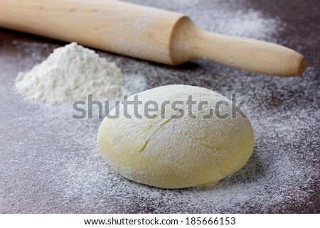 Dough with rolling pin and flour on a stone surface - stock photo