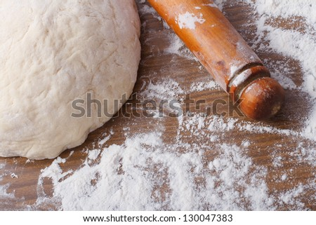 dough with rolling pin on floured table close-up - stock photo