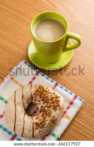 doughnut with nuts and a green mug with coffee - stock photo