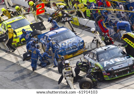 DOVER, DE - SEP 26:  Pit Road gets busy drivers bring their race cars in for service during the AAA 400 race at the Dover International Speedway in Dover, DE on Sep 26, 2010. - stock photo