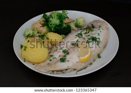 Dover sole fish dinner with potatoes, broccoli (romanesco and traditional), almond slices and lemon - stock photo
