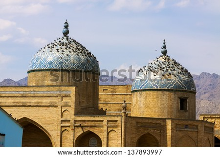 Doves sitting on ancient mosque under blue sky - stock photo