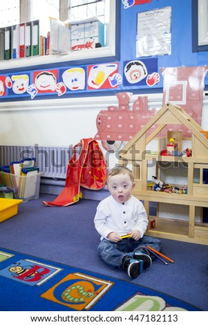 Down Syndrome boy playing with coloring pencils in his nursery classroom. He is looking at the camera. - stock photo