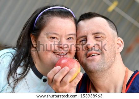 down syndrome couple with apple - stock photo