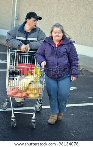 down syndrome couple with shopping cart - stock photo