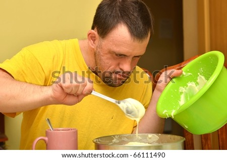 down syndrome man making pudding - stock photo
