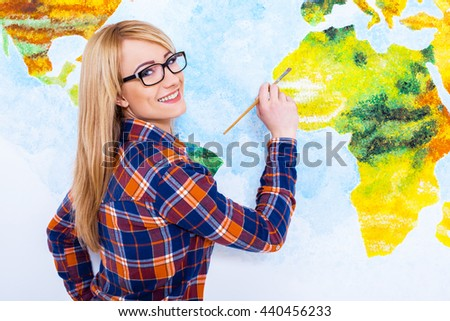 Down to a fine art. Closeup of an attractive  young woman painting the wall - stock photo
