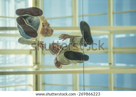 Down view Two teen girl on glass transparent blue floor waving his hand in greeting against roof and blue sky Empty space for inscription Couple of teenager up stand on plastic with smiley face - stock photo