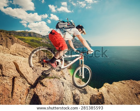 Downhill bike. Down from the mountain on a mountain bicycle on a rocky trail. Extreme sport. Man riding outdoors lifestyle. - stock photo