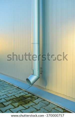 Downspout on the galvanized metal wall. - stock photo