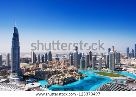 DOWNTOWN DUBAI, UAE - MAY 7 - The Dubai Fountain is set on the 30-acre manmade Burj Khalifa Lake. 63-storey, 302.2 m Address Hotel is visible on the left. Picture taken on May 7, 2010. - stock photo
