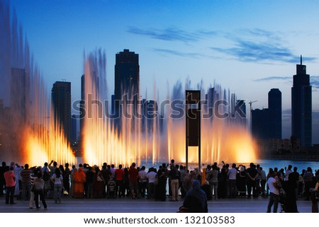 DOWNTOWN DUBAI, UAE - MAY 14: The Dubai Fountain on May 14, 2010 in Dubai, UAE. It is one of UAE most famous attractions, lit by 6600 lights and 50 projectors it shoots water 150 m into the air. - stock photo