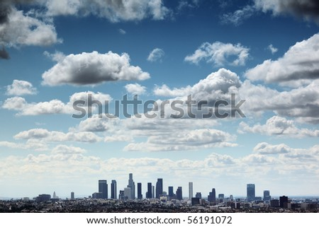 Downtown Los Angeles skyline under blue sky with scenic fluffy clouds. - stock photo