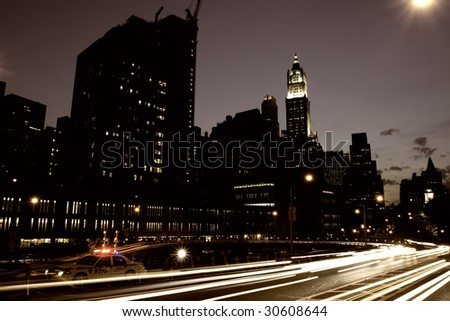 Downtown Manhattan with car light trails and a police car - stock photo