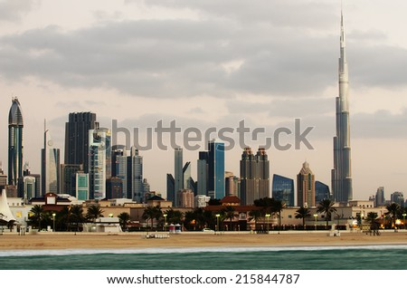 Downtown of Dubai (UAE, United Arab Emirates) in the evening. Beautiful skyline of modern city built in the desert. Burj Khalifa, the tallest building in world.The view from the beach of Persian Gulf - stock photo