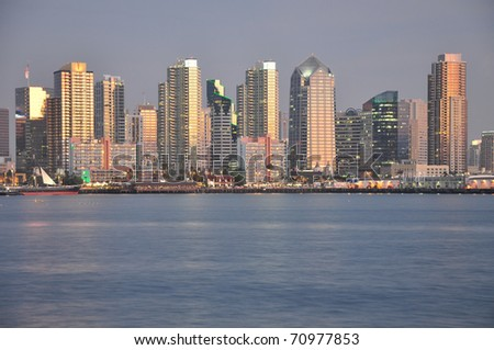 Downtown San Diego towers glow at dusk. - stock photo