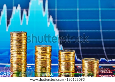 Downtrend financial chart and four stacks of golden coins. Selective focus - stock photo