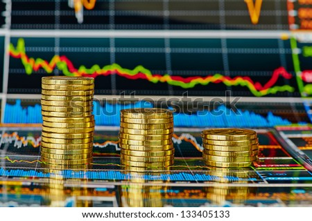 Downtrend financial  chart and stacks of golden coins. Selective focus - stock photo