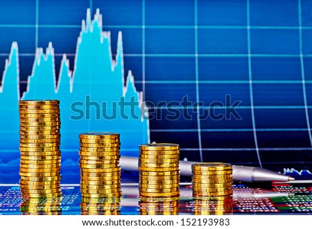 Downtrend financial chart, pen and stacks of golden coins. Selective focus - stock photo