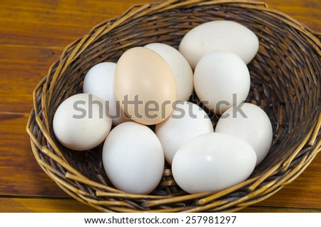 Dozen of white eggs in a wooden basket, placed on a table - stock photo