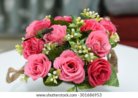 Dragon fly sitting on flower vase with beautiful red flowers. artificial flowers. - stock photo