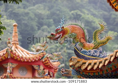 dragon statues in Chinese style on top of general temple roof - stock photo