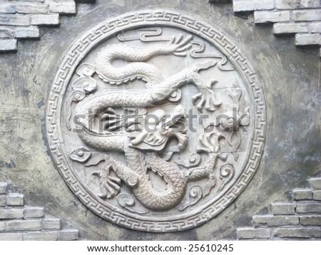 Dragon: Stone sculpture on wall - stock photo