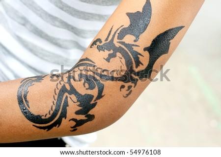 dragon tattoo on female arm - stock photo