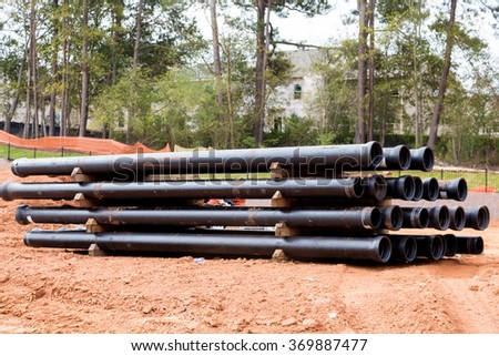 Drain and sewer pipes in dirt at a residential construction site - stock photo