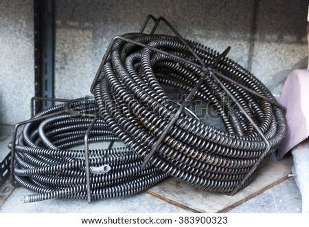 Drain Cleaning cable in storage - stock photo