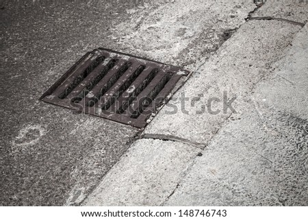 Drainage cover on the road side - stock photo