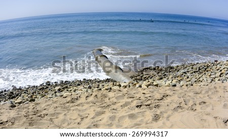 Drainage waste pipe near central San Buenaventura city beach sticking directly into the ocean; wide angle curved horizon - stock photo