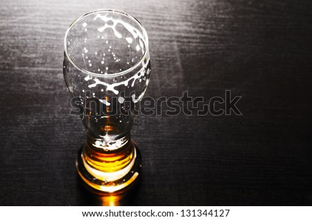 drained glass of fresh lager beer on black table - stock photo
