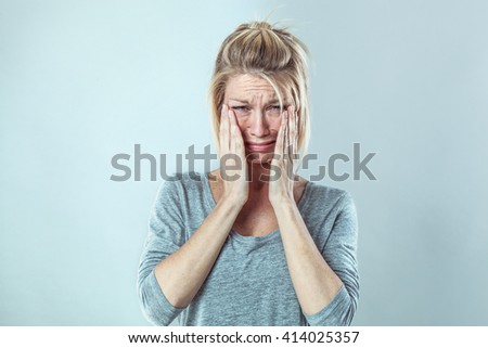 drama concept - desperate young blond woman crying with big tears expressing despair and failure, grey background studio, contrast effects