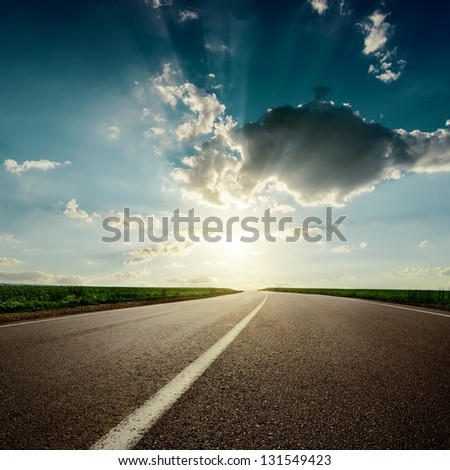 dramaric sunset over asphalt road closeup - stock photo