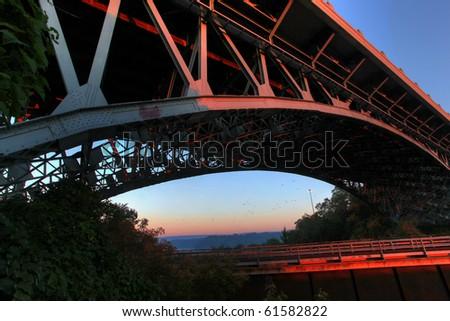 dramatic angle of a bridge against morning sky - stock photo