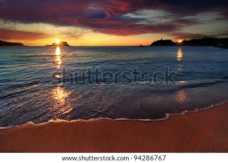 Dramatic beach sunrise with distant building reflection - stock photo