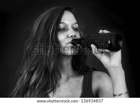 Dramatic black and white portrait of drunk young woman drinking beer over black - stock photo