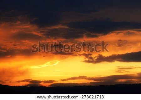 Dramatic blurred sunset sky with orange clouds and bird fly. - stock photo