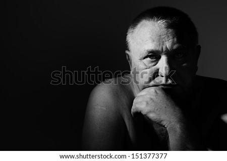 Dramatic close up portrait of depressed old man - stock photo