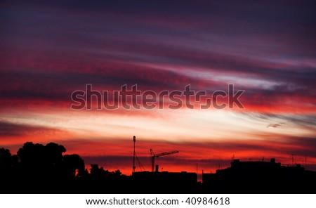 Dramatic cloud scheme at sunset over an urban skyline - stock photo