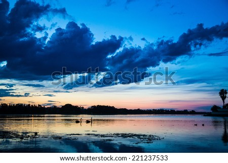 Dramatic clouds after sunset reflecting in the lake - stock photo