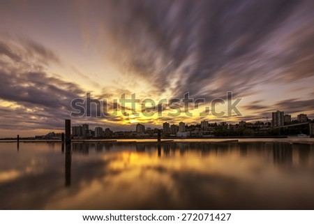 dramatic clouds over city and river at sunset - stock photo