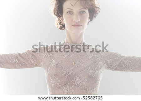 Dramatic cropped portrait of woman indoors with arms outstretched - stock photo
