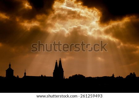 Dramatic dark sky with streaming lights and silhouette of an ancient church in the Czech Republic. - stock photo