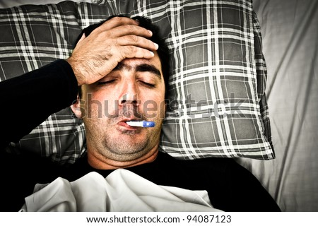 Dramatic desaturated image of a sick man laying in bed with fever - stock photo