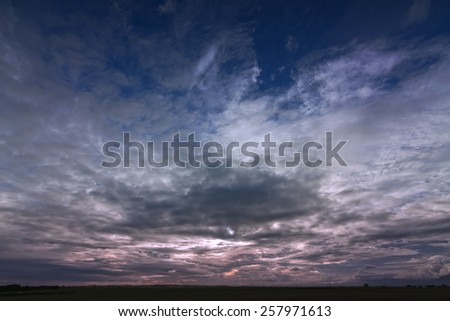 dramatic evening sky filled with clouds as a dramatic background - stock photo