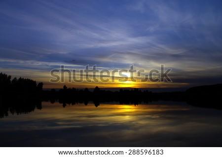 Dramatic evening sky over lake - stock photo