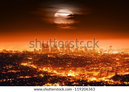 Dramatic full moon over Los Angeles skyline at night. - stock photo